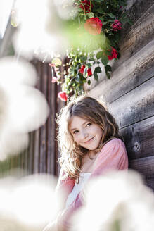 Portrait of smiling girl leaning against wooden wall - STBF00418