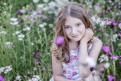 Portrait of smiling girl sitting on a flower meadow - STBF00421