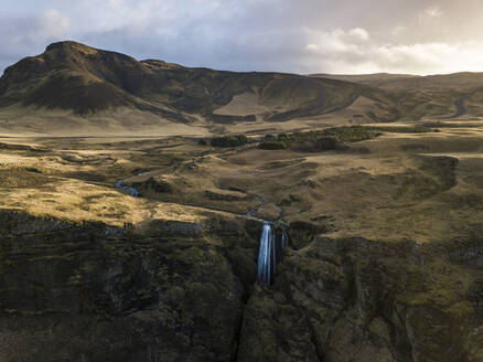 Iceland, Aerial view of waterfall splashing down high cliff - DAMF00076