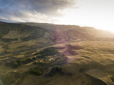 Iceland, Aerial view of empty road across brown hills at sunset - DAMF00079