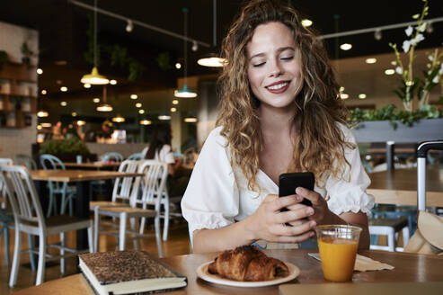 Smiling young woman using smartphone in a cafe while having breakfast - IGGF01332