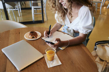 Young woman in a cafe using smartphone and taking notes while having breakfast - IGGF01335
