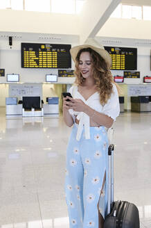 Young woman with baggage using smartphone at the airport departure hall - IGG01338