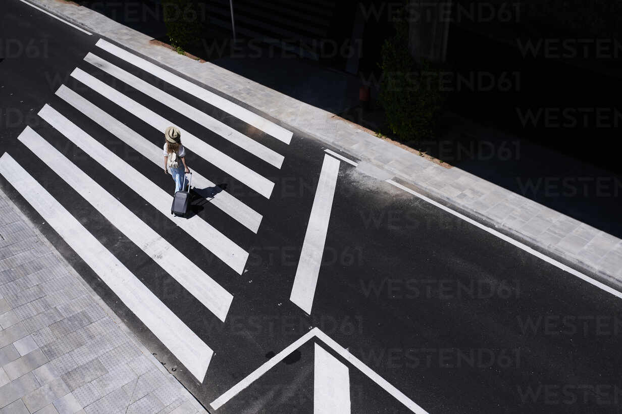 Top view of young woman with baggage crossing a street at the airport - IGGF01341 - Ivan Gener/Westend61