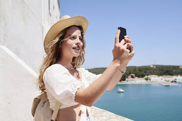 Young woman taking a selfie at the coast, Menorca, Spain - IGGF01344