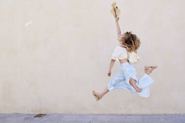 Carefree young woman with hat jumping at a wall - IGGF01353