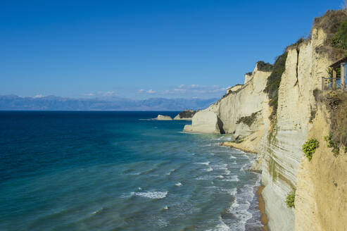 Scenic view of cliff by sea at Loggas beach against blue sky, Corfu, Ionian islands, Greece - RUNF03331