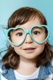 Portrait of cute little girl with heart shaped glasses on blue background - GEMF03176
