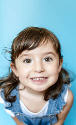 Portrait of cute little girl smiling very expressive on blue background - GEMF03179