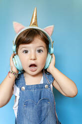 Portrait of cute little girl listening music and singing with unicorn shaped earphones on blue background - GEMF03185