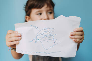 Little girl holding a handmade drawing on blue background - GEMF03191