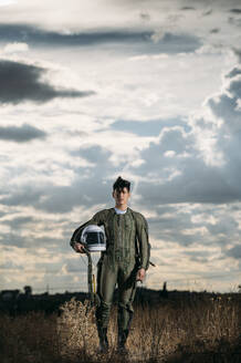 Man dressed as an astronaut on a meadow with dramatic clouds in the background - DAMF00086