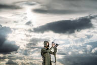 Man posing dressed as an astronaut with dramatic clouds in the background - DAMF00092