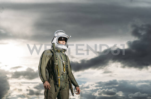 Man posing dressed as an astronaut with dramatic clouds in the background - DAMF00095 - David Agüero Muñoz/Westend61