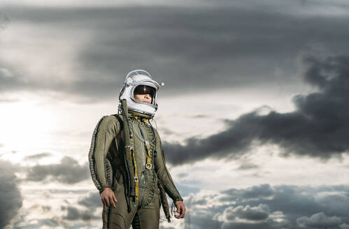 Man posing dressed as an astronaut with dramatic clouds in the background - DAMF00095