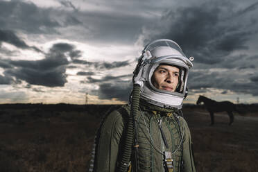 Man posing dressed as an astronaut with dramatic clouds in the background - DAMF00098