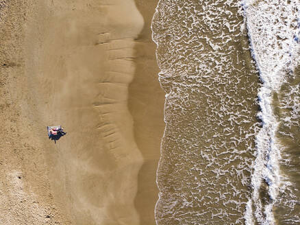 Spain, Sitges, aerial view of mother and daughter lying on sandy beach - PSIF00329
