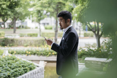 Young businessman with cell phone in the city - JPIF00169
