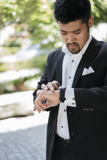 Young businessman in the city checking the time - JPIF00172