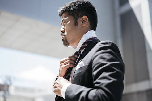 Young businessman in the city adjusting his tie - JPIF00175