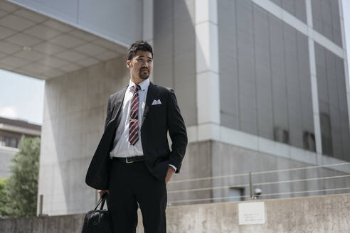 Young businessman in the city looking around - JPIF00178