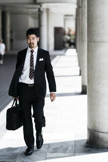 Young businessman walking in the city - JPIF00187