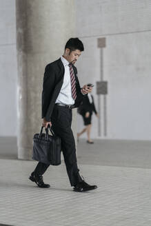 Young businessman with cell phone walking in the city - JPIF00190