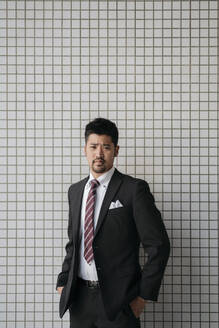 Portrait of confident young businessman at tiled wall - JPIF00193