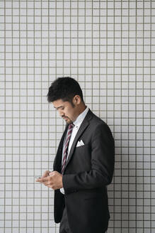 Young businessman using cell phone at tiled wall - JPIF00196
