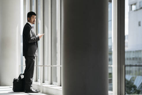 Young businessman with cell phone standing at the window - JPIF00199