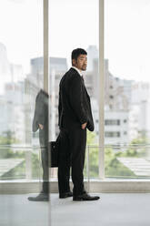 Young businessman standing at the window - JPIF00205