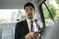 Young businessman with cell phone in a taxi talking to the driver - JPIF00211