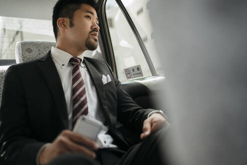 Young businessman with cell phone in a taxi looking out of window - JPIF00214