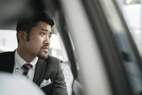 Young businessman in a taxi looking out of window - JPIF00217