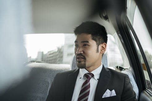 Young businessman in a taxi - JPIF00220