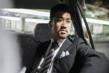 Young businessman in a taxi looking out of window - JPIF00223