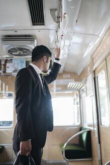Young businessman on a train - JPIF00226