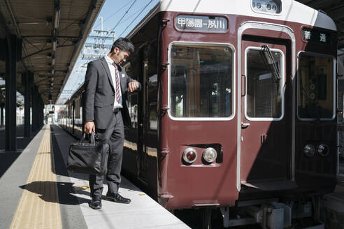 Young businessman on a train platform checking the time - JPIF00232