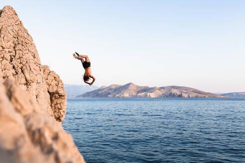 Croatia, Krk, man diving into sea - WVF01438