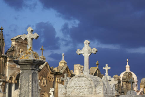 Italy, Sicily, Alcamo, gravestones against moody sky - TLF00767
