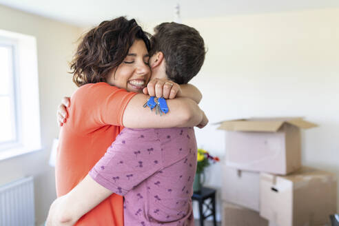 Happy couple hugging in new home - WPEF01925