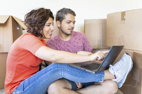 Happy couple moving into new home using laptop - WPEF01928