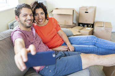 Happy couple taking a selfie on couch in new home - WPEF01934