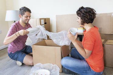 Happy couple moving into new home unpacking cardboard box - WPEF01937