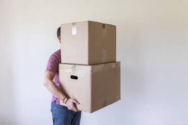 Man moving into new home carrying cardboard boxes - WPEF01940