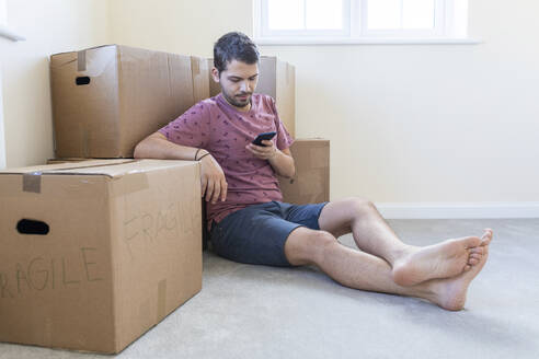 Man using cell phone in new home - WPEF01946