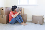 Woman sitting on the floor in new home using cell phone - WPEF01949