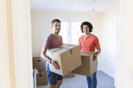 Portrait of happy couple moving into new home carrying cardboard boxes - WPEF01952