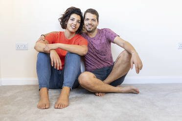 Portrait of happy couple sitting on the floor in new home - WPEF01955