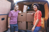 Portrait of smiling couple at van with cardboard boxes - WPEF01961
